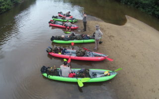 an image of seven adventurers getting kayaks ready for the jungle river