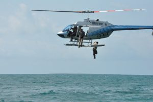 an image of men jumping from a helicopter to arrive at an island survival trip