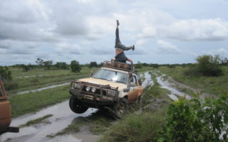 Man balancing upside down on the top of a muddy 4x4