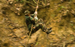 an image of a brave man dressed in camouflage swinging on a vine in the Guyanan jungle