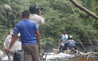 an image of men filming whilst sailing through the jungle river
