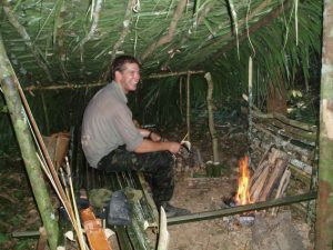 an image of a man sitting in a shelter he built himself during a Bushmasters jungle survival course.