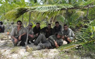 an image of a group of men sitting under their man made shelter
