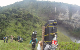 Film crew trekking toward a jungle and waterfall with heavy backpacks