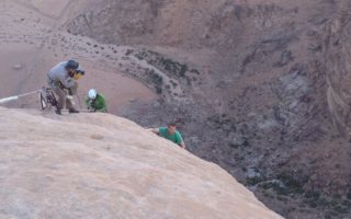 an image of filming explorers abseiling down dessert mountains