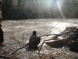 an image of a man sat by a river in the rain during a Bushmasters jungle survival course