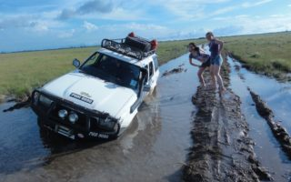 an image of a 4x4 unfortunately stuck in the mud with adventurers looking on and smiling