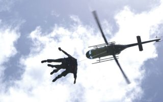 an image of two men jumping out of a hovering helicopter
