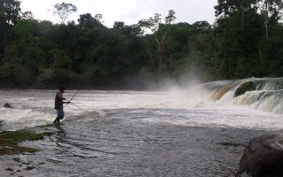 an image of a man aiming his arrow into the water in order to catch his dinner on the Busmasters jungle survival course