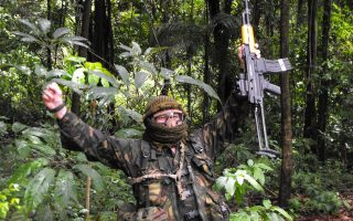 An image of a man with his arms in the air, rejoicing at another successful Jungle Combat course