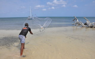 Man throwing fishing net into the shallow ocean