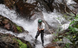 an image of a brave man wearing a helmet abseiling down waterfalls