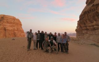 An image of a group of people smiling for the camera in the Jordan desert during the Bushmasters' Desert Venture