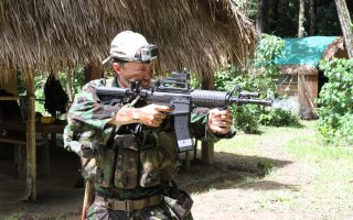 An image of a man dressed in army gear wielding a gun on a Bushmasters jungle combat venture