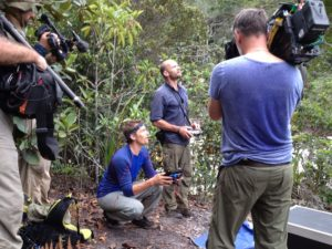 Men using camera equipment whilst filming in the jungle