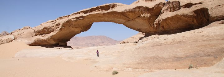 an image of a person standing underneath a sand dune on the Bushmasters desert venture trip