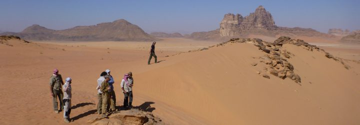 an image of a group of people standing on a sand dune on the Bushmasters desert venture trip