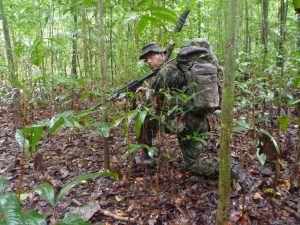 an image of a man wearing army gear crouching in the forest during a Bushmasters Jungle Combat venture
