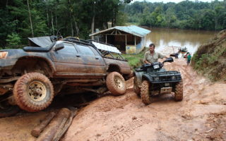 an image of a large 4x4 stuck in the mud in the rainforest