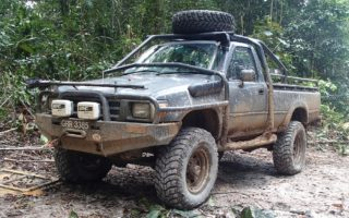 an image of a muddy 4x4 in the middle of the rainforest