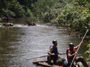 an image of a group of explorers sailing down a jungle river on homemade rafts