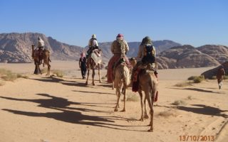 an image of explorers riding camels in the Jordan desert