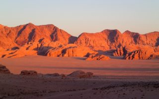Glowing orange desert mountains as the sun goes down