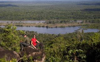 an image of two brave Bushmasters adventurers sitting on rocks amongst the rainforest