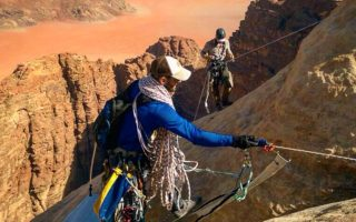 an image of two people abseiling down desert rocks