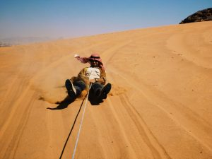 an image of a man sliding down a sand dune on a Bushmasters desert venture