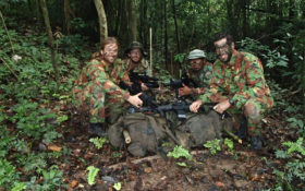 Men smiling in jungle combat gear in the middle of the jungle holding guns