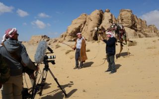 an image of a film crew filming two men and one camel in the rocky desert