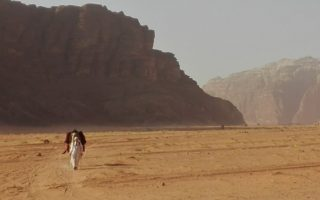 an image of a man and his camel walking through the desert