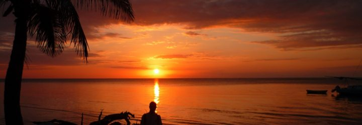 an image of a man standing in front of beautiful orange sunset