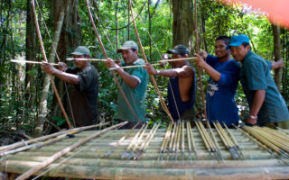 Men practicing at shooting their homemade arrows and smiling during their jungle survival course