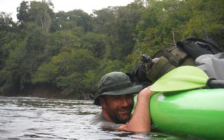 an image of a man smiling whilst tugging along a green kayak carrying his kit