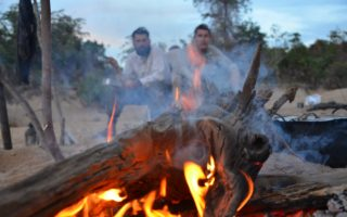an image of two men sat by the campfire at the end of a long day taking part on the Kayak Expedition put together by Bushmasters