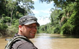 an image of a man looking over his shoulder and smiling at the camera whilst on the Guyana river