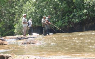 an image of men fishing in the river whilst taking part in our Jungle Survival course