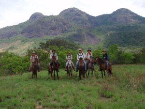 an image of men riding horses on the Bushmasters Ranch Venture