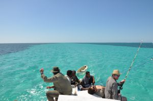 an image of a men on a boat in Belize, travelling around different desert islands