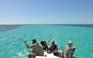 an image of a men on a boat, travelling around different desert islands